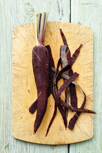 Peeled purple carrot on a chopping board