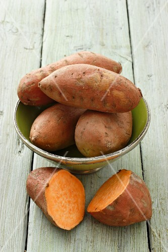 Whole sweet potatoes in a dish, with a halved sweet potato to the front