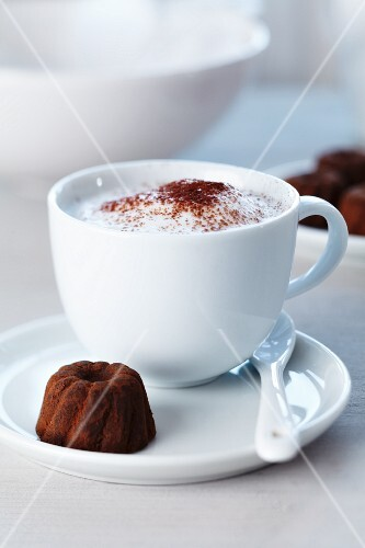 A cup of cappuccino and a praline in the shape of a ring cake