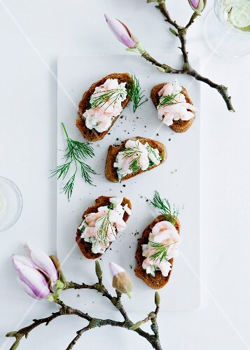 Slices of bread topped with prawns and dill