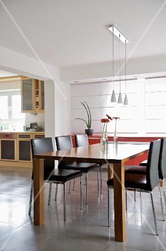Designer dining area in open-plan interior with view of kitchen counter through wide doorway