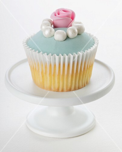 A cupcake decorated with pale blue glaze, sugar pearls and a sugar rose