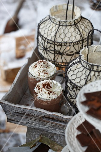 Glasses of hot chocolate and lanterns on a wooden tray
