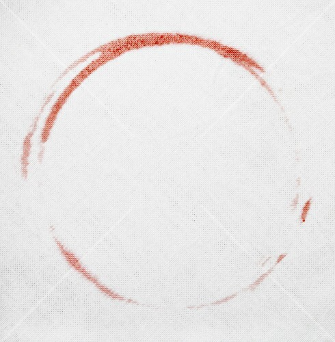 A red wine stain on a white tablecloth