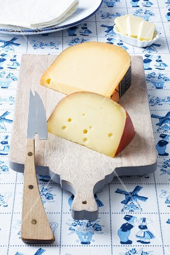 Dutch cheeses (Leerdammer, Old Amsterdam) on a board on a Dutch tablecloth