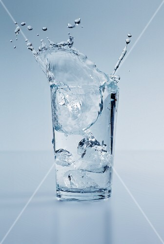 Ice Cubes Splashing into a Glass of Water with a Lemon Wedge
