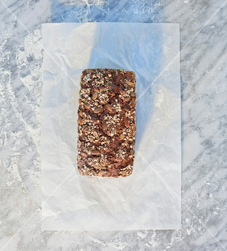 A tin-baked loaf topped with rolled oats, pumpkin seeds and sunflower seeds, on paper, on a marble slab dusted with flour
