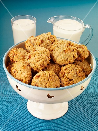 Oat biscuits in a bowl, with a jug of milk and a glass of milk