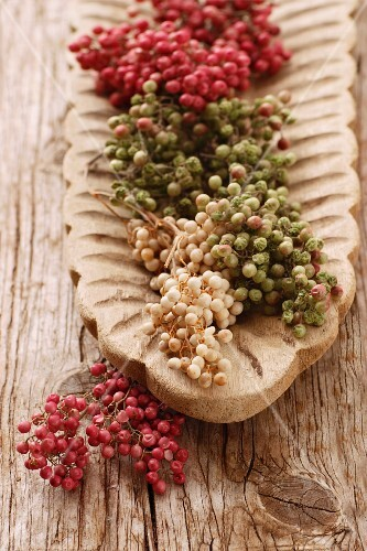 Peppercorns on the vine (red, white and green) in a wooden dish