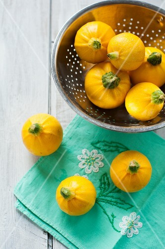 Round yellow courgettes in a colander and on a cloth