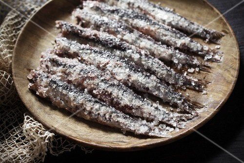 Anchovies covered with sea salt on a wooden plate