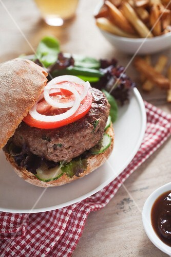 A home-made hamburger with cucumber, tomato and lettuce