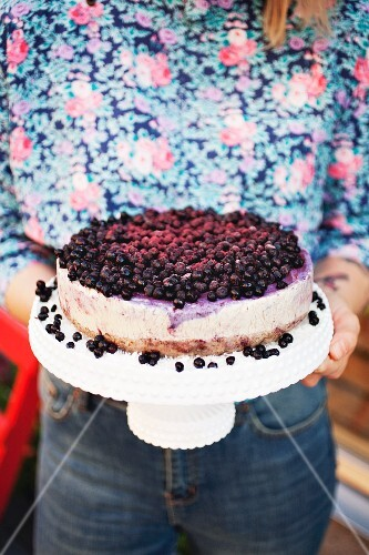 A woman holding a cheesecake with fresh blueberries on a torte stand