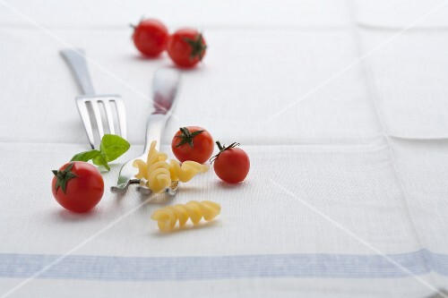 A still life of fusilli, cherry tomatoes and basil