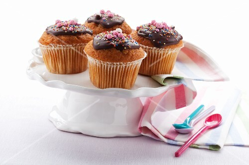 Cupcakes topped with chocolate glaze and sugar pearls