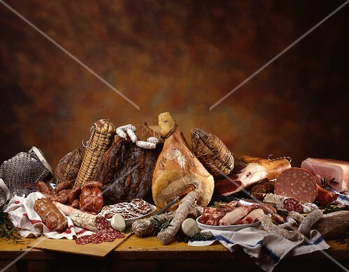 A still life with an assortment of Italian hams, salamis and sausages