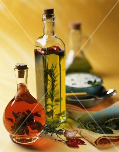 Flavoured oil and vinegar in bottles; a bowl of herb sauce in the background