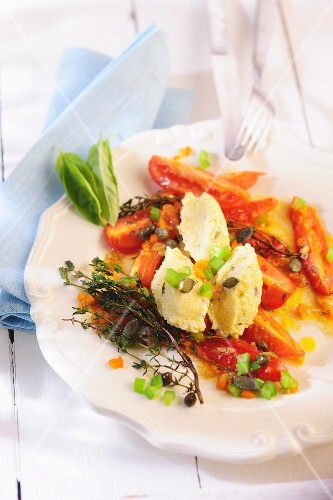 Quenelles of cheese on a plate of tomatoes