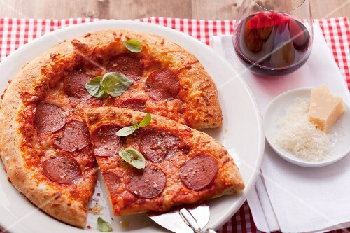 Pizza with salami and basil; one slice of the pizza is on a pizza shovel