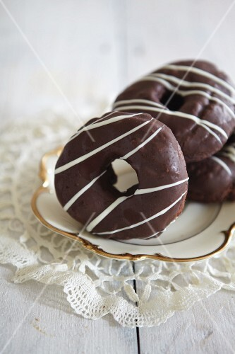 Ring doughnuts dipped in chocolate on a gold-edged plate