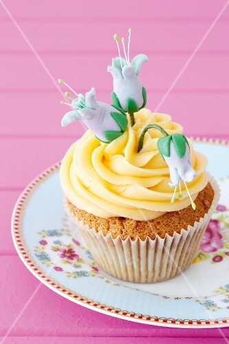 A cupcake decorated with yellow frosting and blue sugar flowers