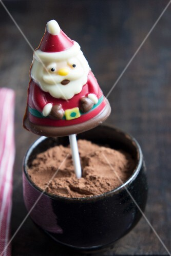 A chocolate Father Christmas on a stick in a bowl of cocoa powder