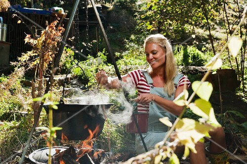 A woman stirring a pot hanging over the campfire