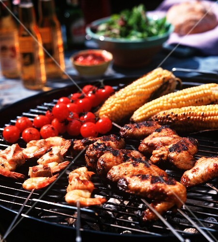 Chicken wings, prawn skewers, baby sweetcorn and tomatoes on the barbecue grill