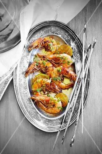 Fried scampi with limes on a silver platter