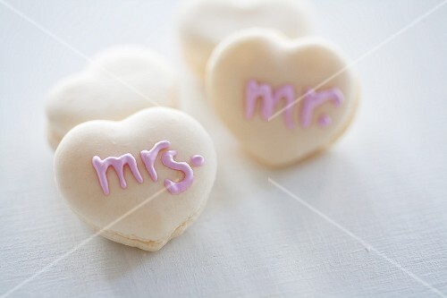 Heart-shaped macaroons decorated with writing using sugar icing
