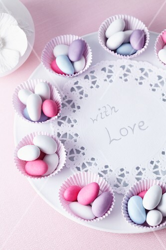 Sugared almonds in muffin cases on a plate with a message of love, for a wedding