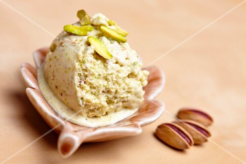 Home-made pistachio ice cream with pistachios as decoration, in a bowl