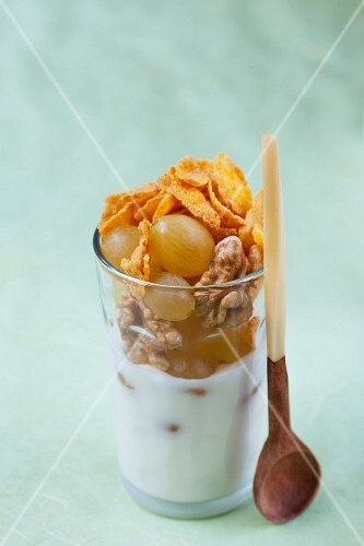 A layered dish of yoghurt, cornflakes and grapes
