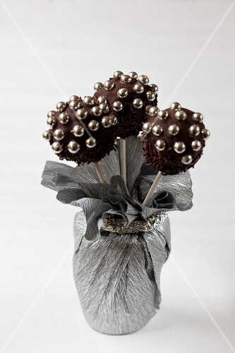 A bunch of chocolate cake pops with sugar pearls