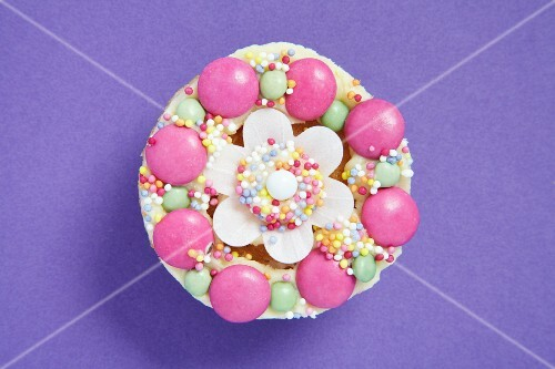 Cupcake decorated with colourful chocolate beans and sugar strands