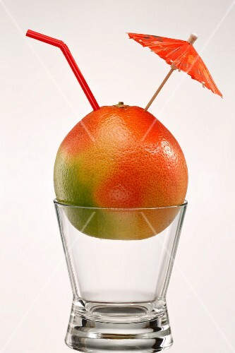 A grapefruit on a glass with a cocktail umbrella and a drinking straw