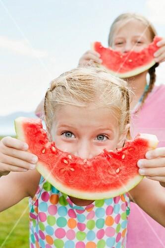 Girls (6-7, 8-9) eating watermelon