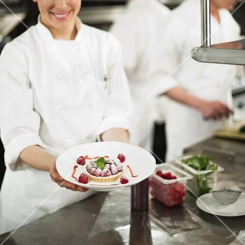 Chefs preparing food in kitchen, women showing dessert
