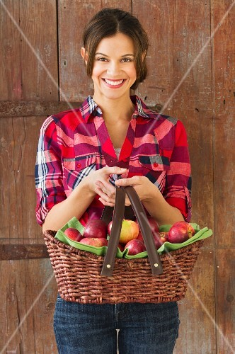 Smiling woman holding basket full of apples