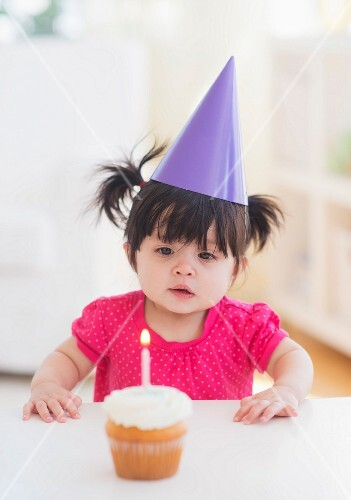 Portrait of baby girl (12-17 months) in party hat with cupcake