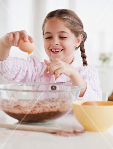 Young girl cracking egg