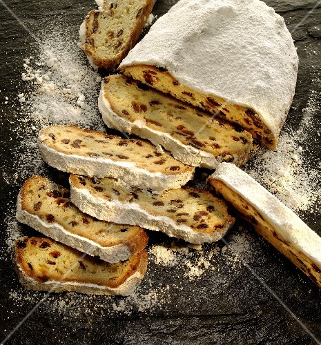 Christmas stollen dusted with icing sugar, partly sliced