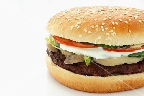 A hamburger with mushrooms, mozzarella and tomatoes