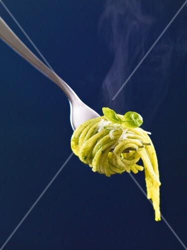 Spaghetti with basil pesto on a fork (close up)