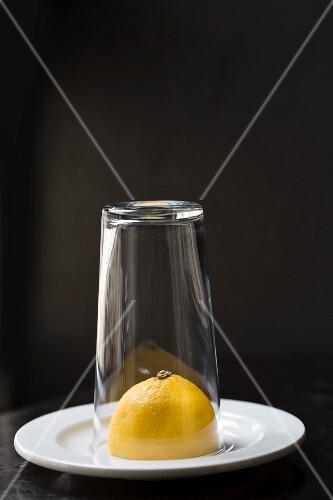 Half a lemon under a glass on a white plate