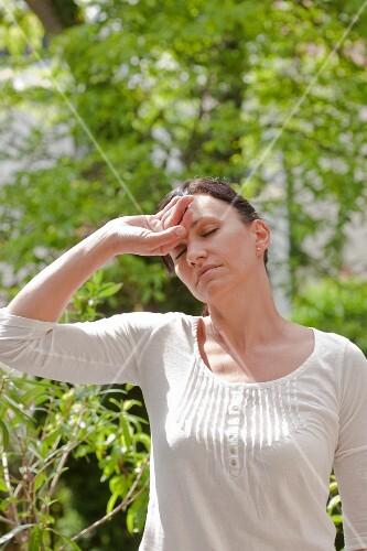 Women with a headache in the garden