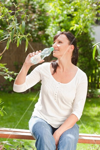 Woman drinking water on a garden bench