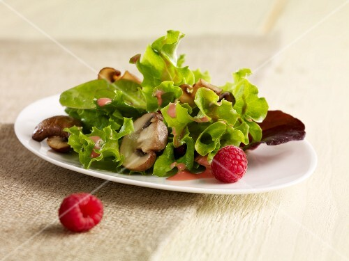 Green salad with pan fried mushrooms, raspberries and raspberry dressing