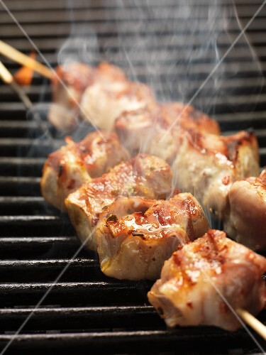 Barbecued skewers of pork wrapped in bacon