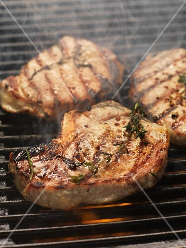 Barbecued pork steaks with herbs on the barbecue